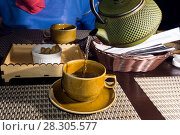 Green tea from a old shabby cast iron kettle is poured into a cup closeup on a blurred background of the second full cup on the opposite side of the table. Стоковое фото, фотограф Евгений Харитонов / Фотобанк Лори