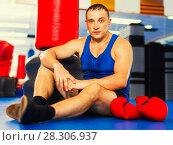 Купить «Man boxer is resting on the floor after training in gym.», фото № 28306937, снято 21 августа 2017 г. (c) Яков Филимонов / Фотобанк Лори