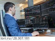Купить «Stock broker trading online watching charts and data analyses on multiple computer screens.», фото № 28307181, снято 2 апреля 2020 г. (c) Matej Kastelic / Фотобанк Лори