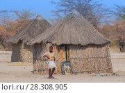 Купить «Local woman near a typical thatched-roof African round hut in Botswana», фото № 28308905, снято 25 апреля 2018 г. (c) BE&W Photo / Фотобанк Лори
