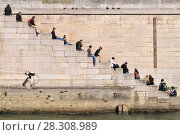 Купить «People relaxing on steps by the river Seine in Paris, France», фото № 28308989, снято 22 октября 2019 г. (c) BE&W Photo / Фотобанк Лори