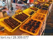 Купить «Food at the Donghuamen Night Market near Wangfujing Street in Beijing, China», фото № 28309077, снято 26 июня 2019 г. (c) BE&W Photo / Фотобанк Лори