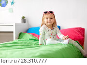 Купить «smiling little girl with sunglasses on bed at home», фото № 28310777, снято 15 октября 2017 г. (c) Syda Productions / Фотобанк Лори
