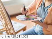 Купить «artist with palette and brush painting at studio», фото № 28311005, снято 1 июня 2017 г. (c) Syda Productions / Фотобанк Лори