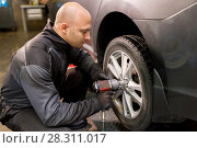 auto mechanic with screwdriver changing car tire. Стоковое фото, фотограф Syda Productions / Фотобанк Лори