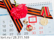 Купить «9 May festive card - jubilee medals of Great patriotic war with red carnations and St George ribbon», фото № 28311169, снято 7 апреля 2017 г. (c) Зезелина Марина / Фотобанк Лори