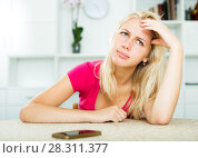 Купить «Irritated girl waiting for call sitting indoors», фото № 28311377, снято 17 августа 2018 г. (c) Яков Филимонов / Фотобанк Лори