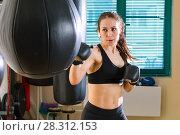 Купить «Женщина бьет боксерскую грушу на тренировке», фото № 28312153, снято 21 марта 2018 г. (c) Владимир Мельников / Фотобанк Лори