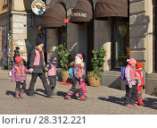 Купить «Little children with teacher go along street», фото № 28312221, снято 27 марта 2018 г. (c) Валерия Попова / Фотобанк Лори