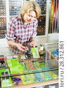 Купить «woman seller standing at counter with various scissors in sewing store», фото № 28312861, снято 19 января 2019 г. (c) Яков Филимонов / Фотобанк Лори
