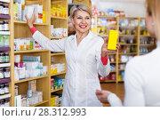 Купить «Mature female seller suggesting care products to young customer», фото № 28312993, снято 15 марта 2017 г. (c) Яков Филимонов / Фотобанк Лори