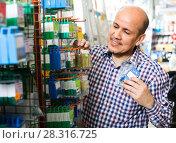 Купить «Customer buying nails and clinkers in store», фото № 28316725, снято 18 ноября 2018 г. (c) Яков Филимонов / Фотобанк Лори