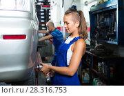 Купить «woman technician fitting new tires to car at workshop», фото № 28316753, снято 19 сентября 2019 г. (c) Яков Филимонов / Фотобанк Лори