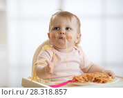 Cute baby toddler girl eating spaghetti with tomato sauce sitting in a white sunny room with big window. Стоковое фото, фотограф Оксана Кузьмина / Фотобанк Лори