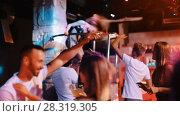 Купить «Group of smiling people clubbing in the night club with drinks», видеоролик № 28319305, снято 7 сентября 2017 г. (c) Яков Филимонов / Фотобанк Лори