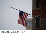 Приспущенный американский флаг на фоне серого неба. Здание генерального консульства во Владивостоке. Стоковое фото, фотограф syngach / Фотобанк Лори