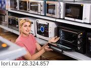 Купить «Positive female looking new microwave for kitchen in furniture store», фото № 28324857, снято 1 марта 2018 г. (c) Яков Филимонов / Фотобанк Лори