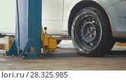 Купить «Car in auto service lifting for repairing, mechanics in garage», фото № 28325985, снято 24 апреля 2018 г. (c) Константин Шишкин / Фотобанк Лори