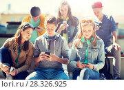 Купить «happy teenage friends with smartphones outdoors», фото № 28326925, снято 21 мая 2016 г. (c) Syda Productions / Фотобанк Лори