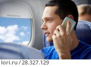 Купить «young man calling on smartphone in plane», фото № 28327129, снято 21 октября 2015 г. (c) Syda Productions / Фотобанк Лори