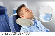 man sleeping in plane with cervical neck pillow. Стоковое фото, фотограф Syda Productions / Фотобанк Лори
