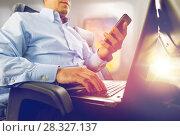 Купить «businessman with smartphone and laptop in plane», фото № 28327137, снято 21 октября 2015 г. (c) Syda Productions / Фотобанк Лори
