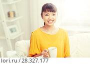 Купить «happy asian woman drinking from tea cup», фото № 28327177, снято 9 марта 2016 г. (c) Syda Productions / Фотобанк Лори