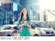 happy young woman drinking coffee on city street. Стоковое фото, фотограф Syda Productions / Фотобанк Лори