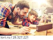 Купить «dad and son with ruler measuring plank at workshop», фото № 28327221, снято 14 мая 2016 г. (c) Syda Productions / Фотобанк Лори