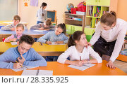 Купить «Teacher woman helping children during lesson in schoolroom», фото № 28335925, снято 28 января 2018 г. (c) Яков Филимонов / Фотобанк Лори