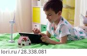 Купить «boy with tablet pc and wind turbine toy at home», видеоролик № 28338081, снято 20 апреля 2018 г. (c) Syda Productions / Фотобанк Лори