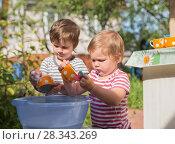 Купить «Two children washing dishes outdoors», фото № 28343269, снято 9 августа 2017 г. (c) Юлия Бабкина / Фотобанк Лори