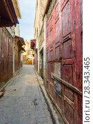 Купить «Old street with red door in Fes medina», фото № 28343465, снято 16 февраля 2018 г. (c) Михаил Коханчиков / Фотобанк Лори