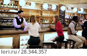 Купить «Handsome hispanic barman serving drinks to young people on bar in restaurant», видеоролик № 28344357, снято 27 марта 2018 г. (c) Яков Филимонов / Фотобанк Лори