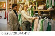 Купить «Couple is choosing jeans clothes for her in the clothes store.», видеоролик № 28344417, снято 27 марта 2018 г. (c) Яков Филимонов / Фотобанк Лори