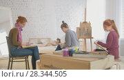 Купить «Young women artists painting picture in art studio», видеоролик № 28344505, снято 25 июня 2018 г. (c) Константин Шишкин / Фотобанк Лори