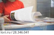 Купить «Hands of female worker in typography turning printed pages», фото № 28346041, снято 22 июля 2018 г. (c) Константин Шишкин / Фотобанк Лори