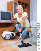 Купить «Housewife vacuuming at home», фото № 28347625, снято 19 января 2019 г. (c) Яков Филимонов / Фотобанк Лори
