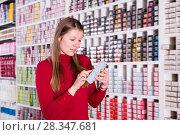 Купить «Ordinary woman is choosing new hair dye», фото № 28347681, снято 22 марта 2018 г. (c) Яков Филимонов / Фотобанк Лори