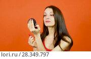 Купить «Studio Portrait of Pretty Woman in Red Top Using Bright Lipstick and Holding Little Mirror in Hand on Orange Background, Perfect Skin Concept», видеоролик № 28349797, снято 28 апреля 2018 г. (c) Ольга Балынская / Фотобанк Лори