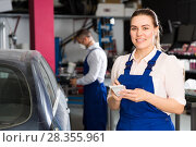 Купить «Girl mechanic taking notes on notebook», фото № 28355961, снято 4 апреля 2018 г. (c) Яков Филимонов / Фотобанк Лори