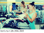 Купить «Young happy females selecting new basics pants», фото № 28356369, снято 19 июня 2017 г. (c) Яков Филимонов / Фотобанк Лори