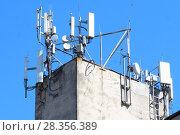 Купить «Антенны базовой станции оператора сотовой связи на крыше здания», фото № 28356389, снято 1 мая 2018 г. (c) Алексей Букреев / Фотобанк Лори