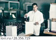 Купить «Man standing in packing section on winemaking factory», фото № 28356729, снято 21 сентября 2016 г. (c) Яков Филимонов / Фотобанк Лори