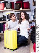Купить «Couple choosing travel suitcase in shop», фото № 28358797, снято 23 сентября 2018 г. (c) Яков Филимонов / Фотобанк Лори