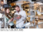 Купить «Smiling couple customers choosing desk lamp», фото № 28361445, снято 29 января 2018 г. (c) Яков Филимонов / Фотобанк Лори