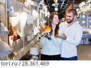 Купить «Smiling couple customers choosing bedside lamp in furniture store», фото № 28361469, снято 29 января 2018 г. (c) Яков Филимонов / Фотобанк Лори