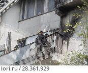 Купить «Хранящийся на балконе жилого дома газовый баллон взорвался из-за брошенного сверху окурка. Пожарный тушит очаг возгорания», фото № 28361929, снято 30 апреля 2018 г. (c) Сайганов Александр / Фотобанк Лори