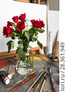 Купить «A bouquet of red roses in a glass vase stands in the artist's studio on a palette with oil paints and brushes. Artistic still life», фото № 28361949, снято 3 мая 2018 г. (c) Виктория Катьянова / Фотобанк Лори