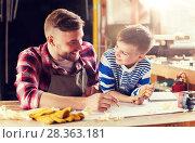 Купить «happy father and son with blueprint at workshop», фото № 28363181, снято 14 мая 2016 г. (c) Syda Productions / Фотобанк Лори